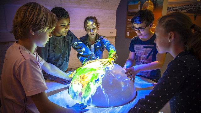 Kinderen zijn aan het ontdekken met een wereldbol bij Geofort in Herwijnen