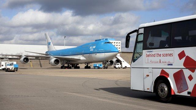 De bus van Schiphol Experience rijdt langs een KLM vliegtuig