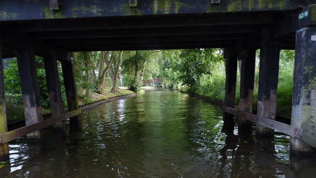 Varen met een rondvaartboot door Giethoorn onder bruggetjes door