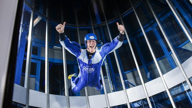 Skydivende man steekt duimen omhoog