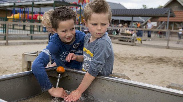 Kinderen spelen met water bij speelboerderij de Flierefluiter