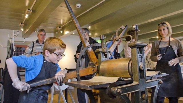 Jongen demonstreert de etspers in Het Rembrandthuis