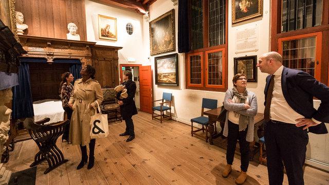 Mensen bekijken schilderijen bij de opening van het rembrandthuis