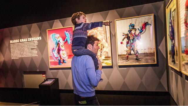 Vader met zoon op zijn nek die wijst naar schilderijen