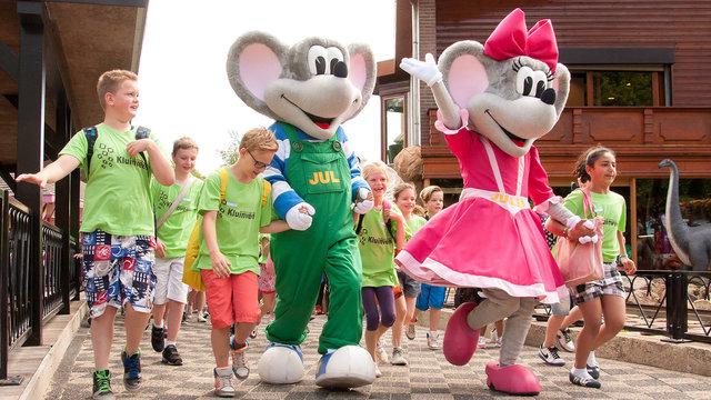 Groep kinderen hand in hand met de mascottes van Julianatoren tijdens een schoolreisje