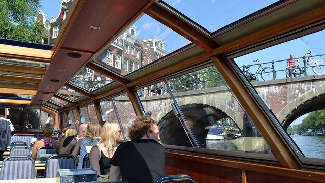 Stelletje kijkt uit raam bij Blue Boat Rondvaart Amsterdam