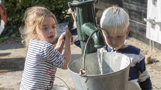 Kinderen kunnen water putten bij het Nederlands Openluchtmuseum.