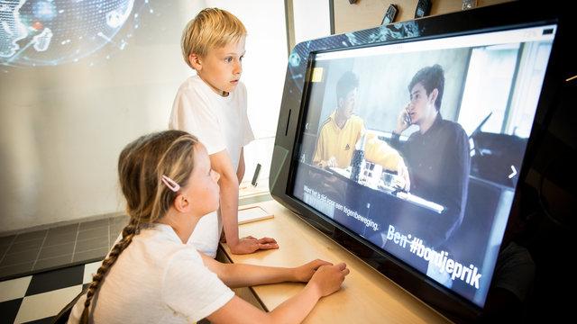 Kinderen kijken naar scherm in COMM.