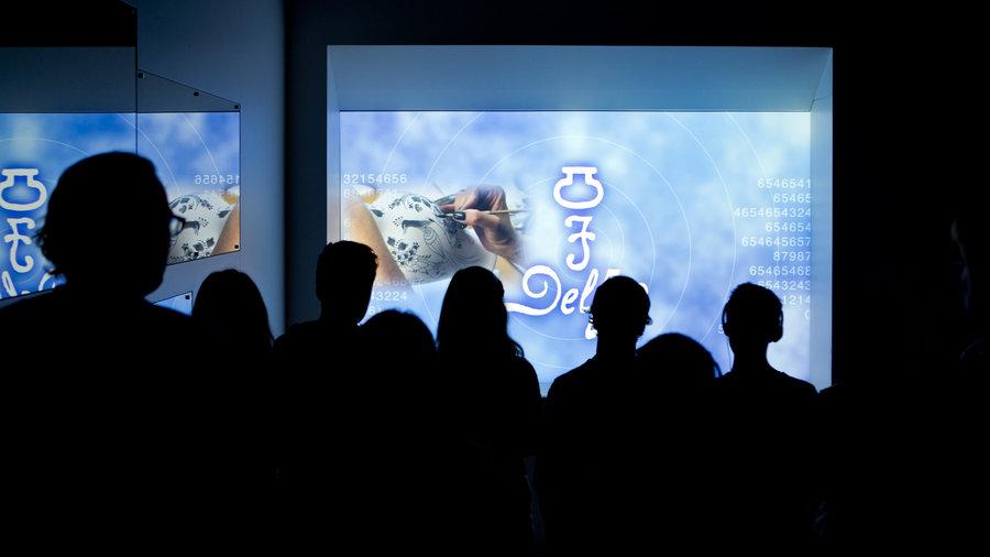 Een groep mensen bekijkt een interactieve presentatie over porselein