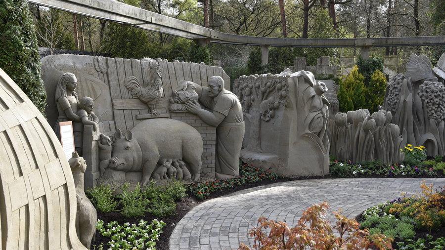 Zandsculpturen van een boerenritueel met een varken een haan en een boer