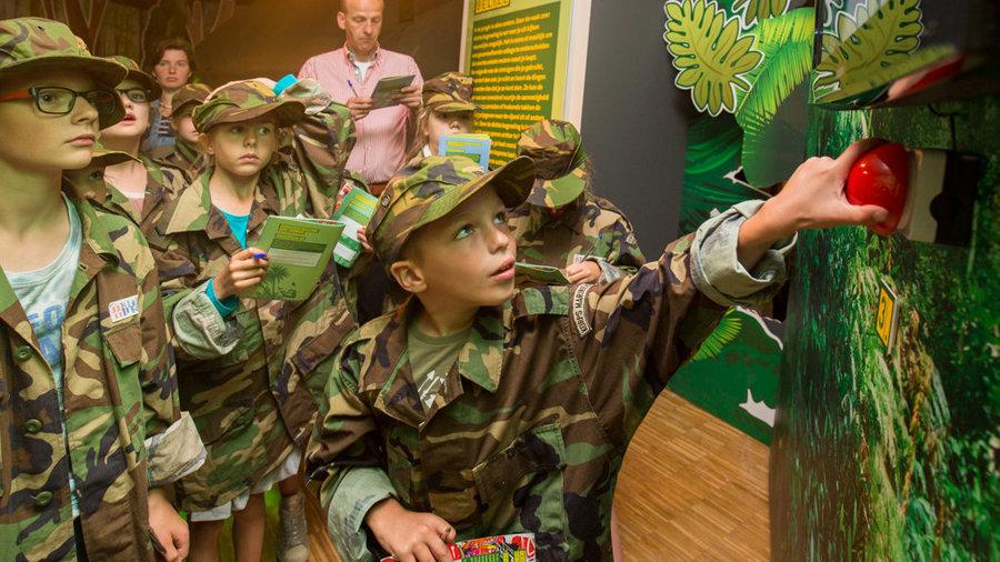 Speurtocht met kinderen in camouflage die op een knop duwen