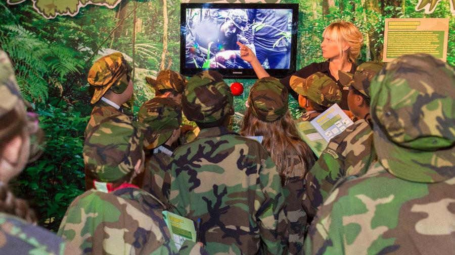 Kinderen op speurtocht die naar een film kijken bij Mariniers Museum