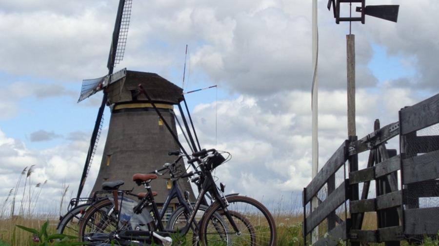 Fietsen door Nederlands landschap met molen