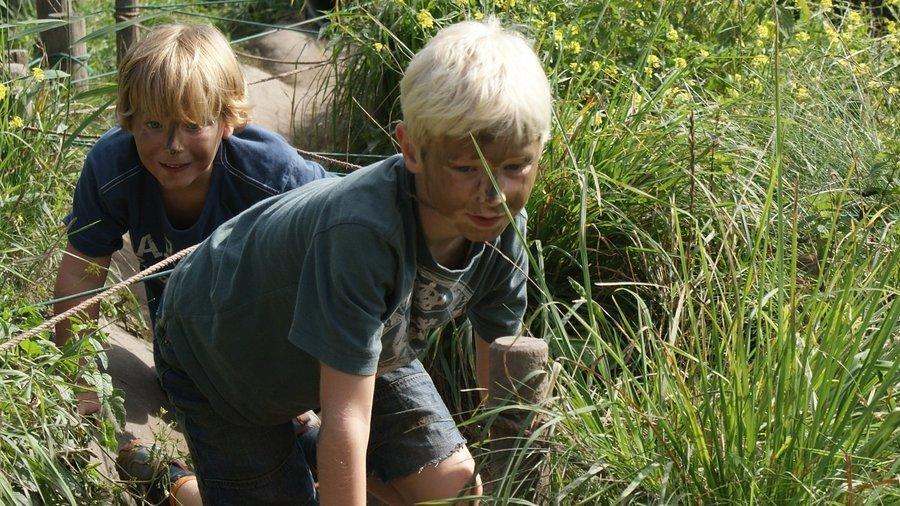 Twee jongens kruipen door een tunnel naar buiten