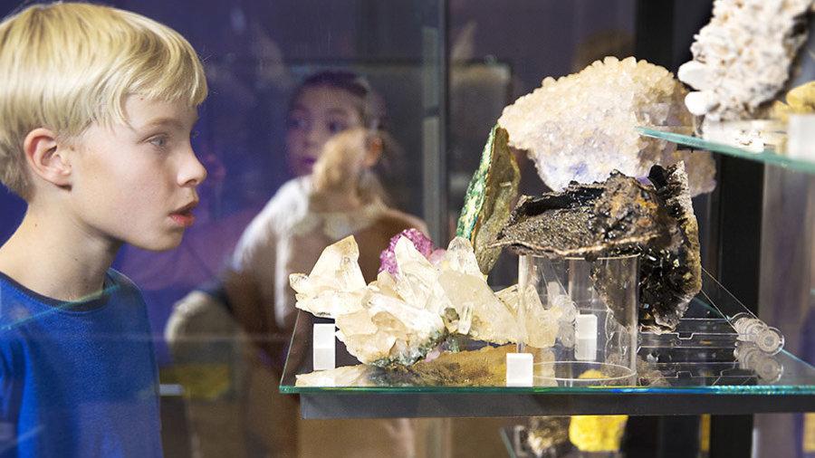 Jongen bekijkt vitrine vol kristallen in Museon