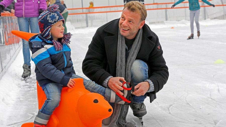 Vader bindt schaatsen onder bij zoon