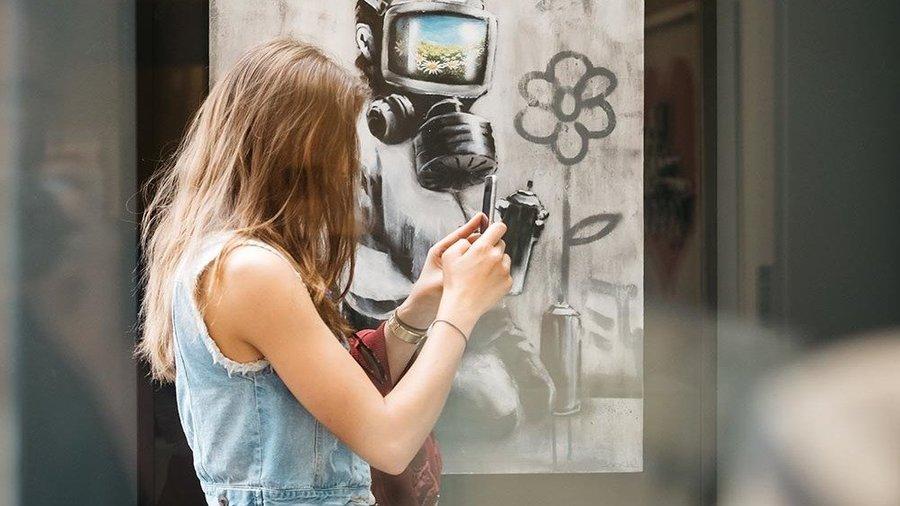 Vrouw bekijkt kunstwerk van Banksy in Moco Museum