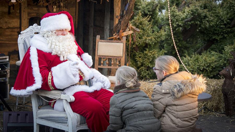 De kerstman vertelt kinderen verhalen op de Country & Christmas Fair