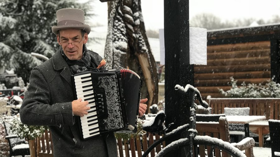 Man in sneeuw met accordeon