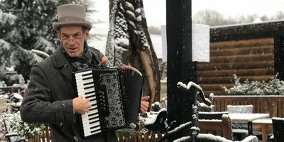Meneer in de sneeuw met accordeon
