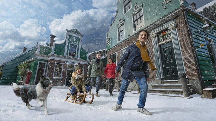 Gezin in de sneeuw met hond en slee