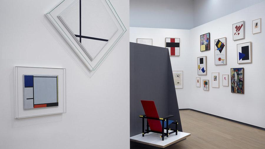 Zaal in Stedelijk Museum Amsterdam vol moderne kunst van o.a. Mondriaan en Rietveld