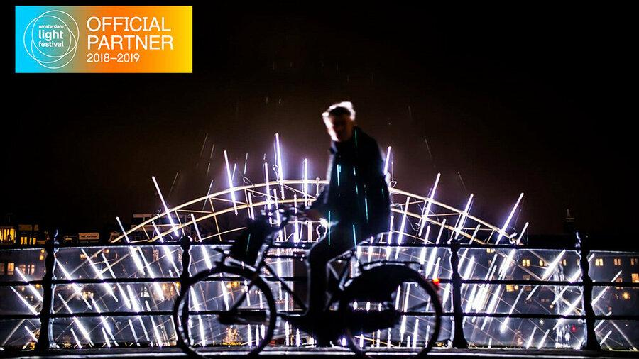 Fietser bij lichtkunstwerk. A-Bike is officieel partner van Amsterdam Light Festival