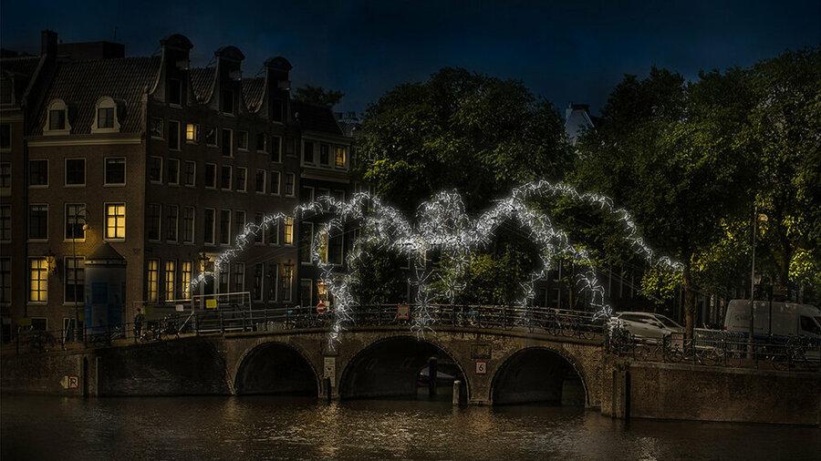 Lichtkunstwerk in Amsterdam: lichtgevende spin op gracht. Amsterdam Light Festival