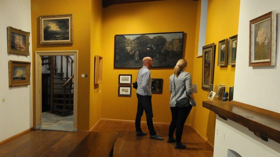Man en vrouw bekijken schilderijen in Voerman Museum