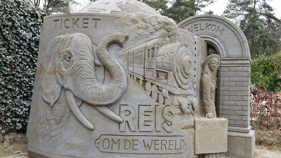 Sculptuur van zand met trein, olifant en een mevrouw met koffer