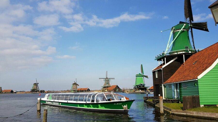 Rondvaartboot en groene molens