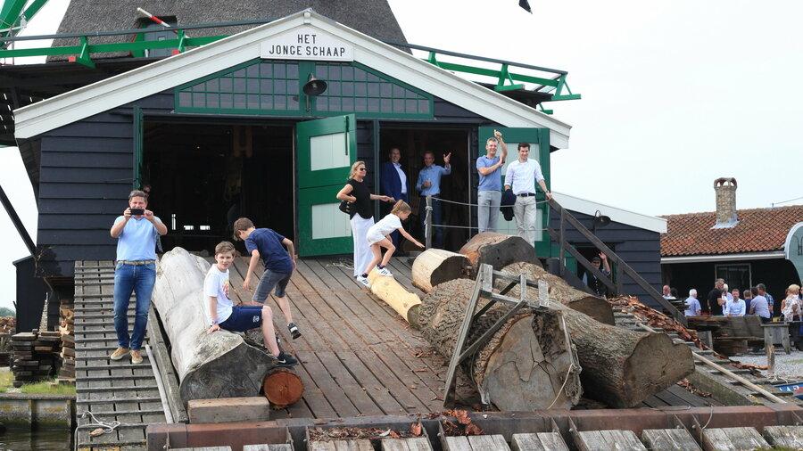 Groep mensen bij een houtmolen