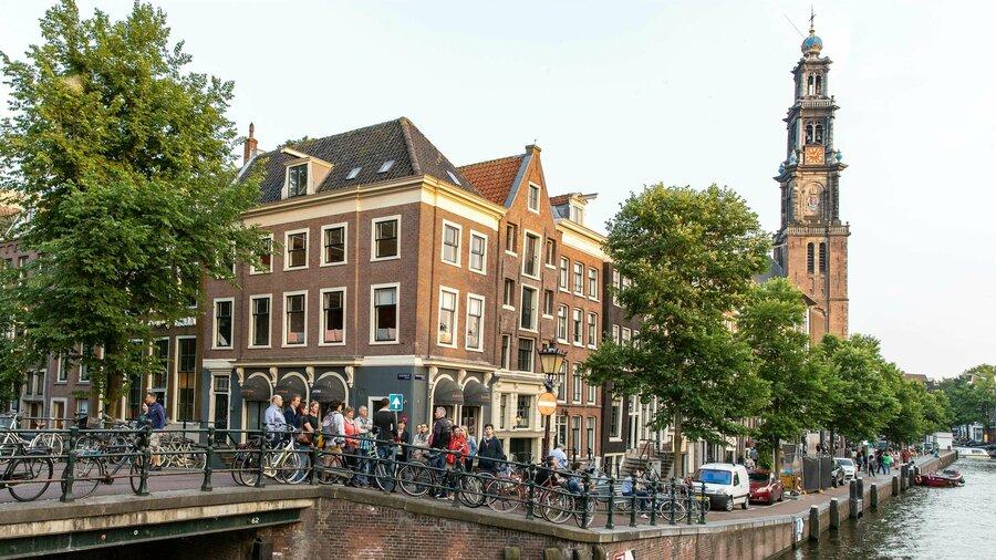 Groep mensen langs een gracht in Amsterdam