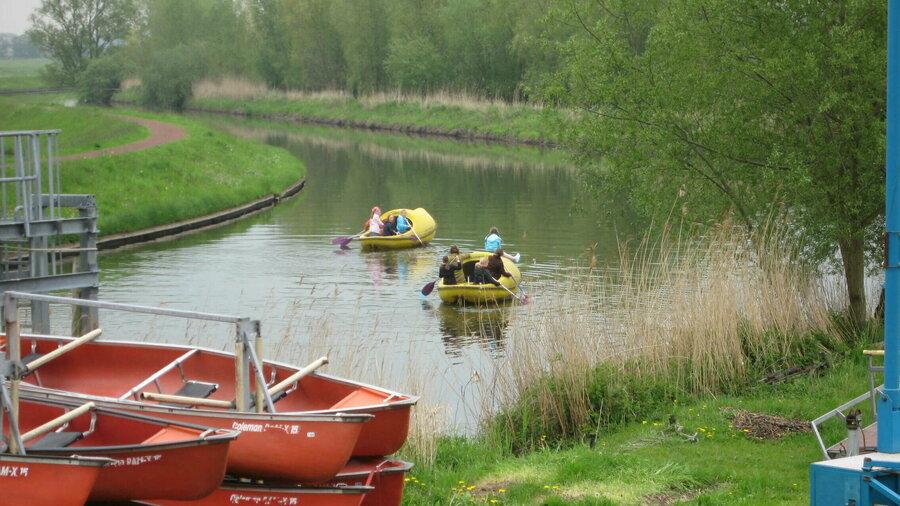 Twee klompboten in het water met kano's op de voorgrond.