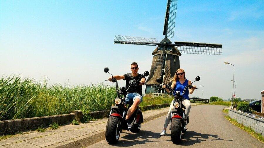 Jongen en meisje op e-scooter bij molen