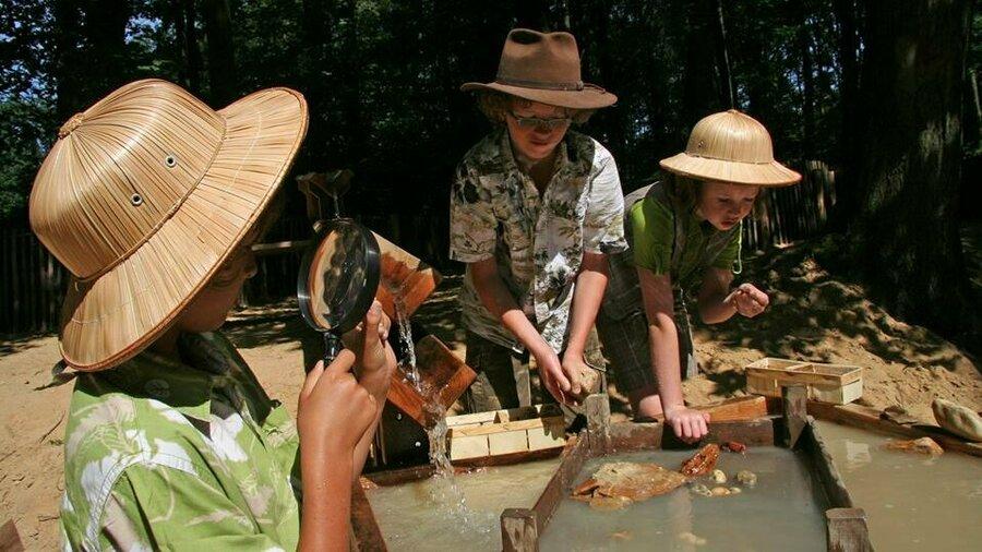 Kinderen bestuderen water en zand met vergrootglas