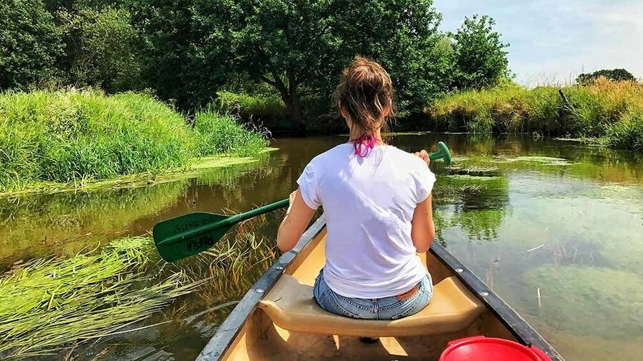 Een vrouw in een Canadese kano op de Dommel