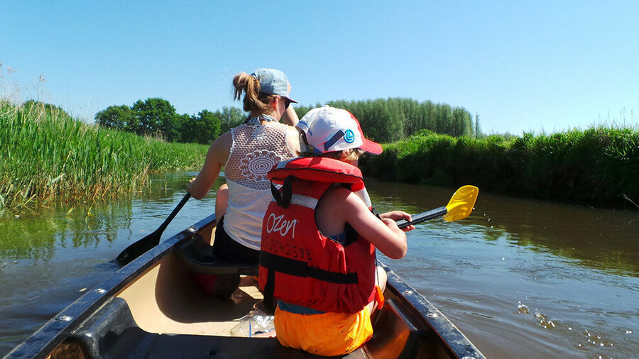 Moeder met kind in Canadese kano op de Dommel