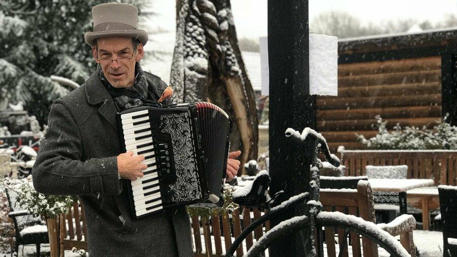 Man in Dickens-kleding speelt accordeon in de sneeuw