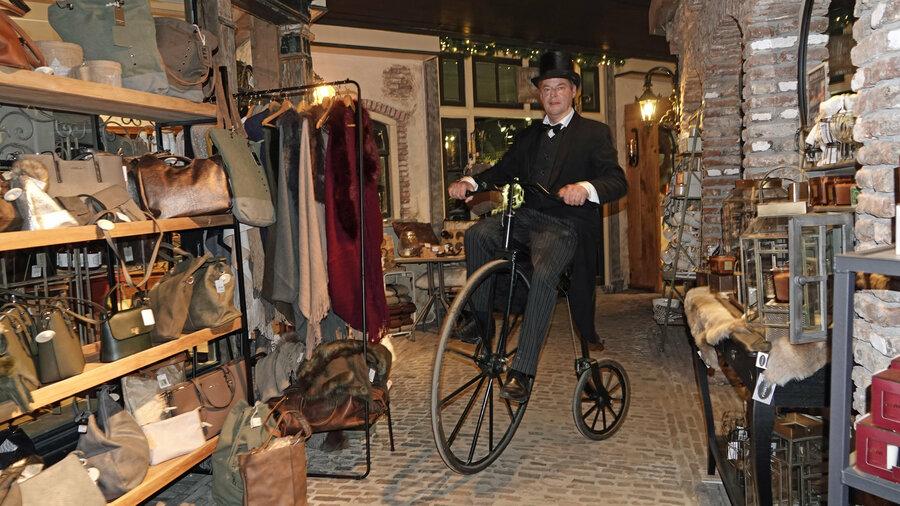 Meneer in Dickensstijl op een ouderwetse fiets