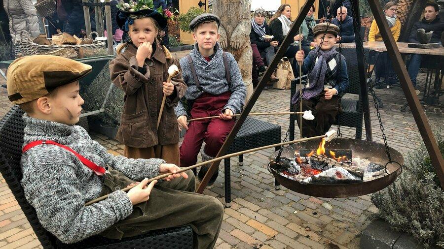 Kinderen roosteren marshmallows boven een kampvuur