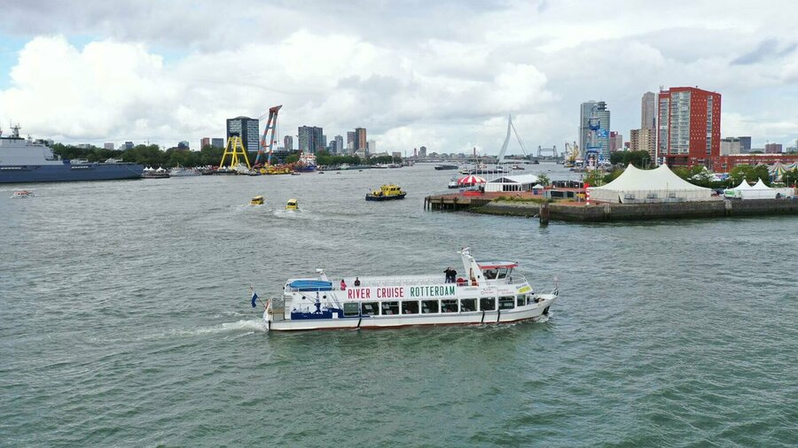 De boot van River Cruise Rotterdam in de Rotterdamse haven met watertaxi's en de Erasmusbrug.