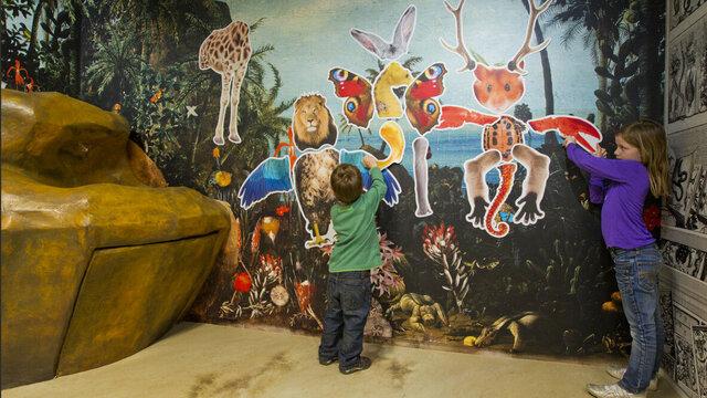 Kinderen bij een wand met rare dieren