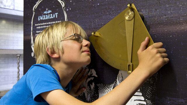 Jongen meet sterren met een kwadrant