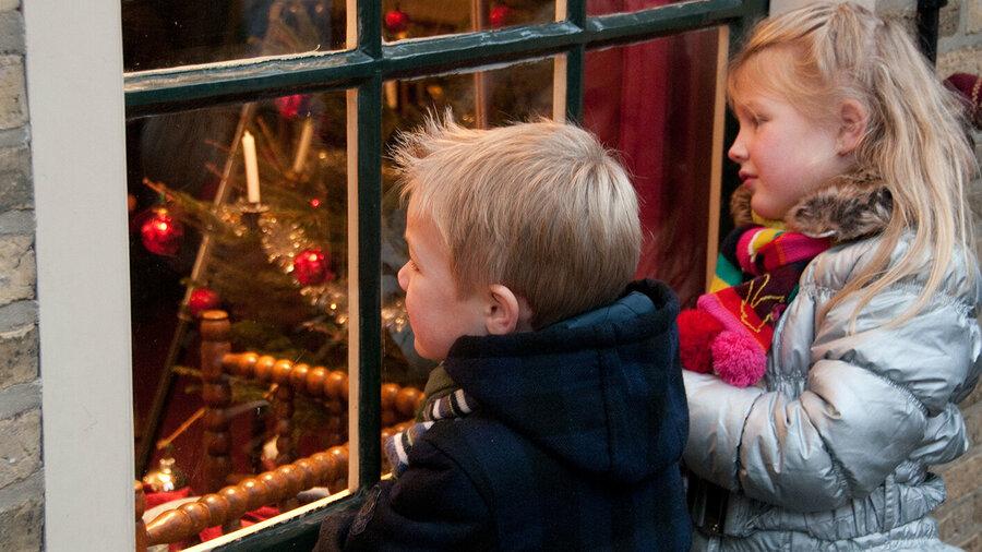 Kinderen kijken een huiskamer in met kerstversiering