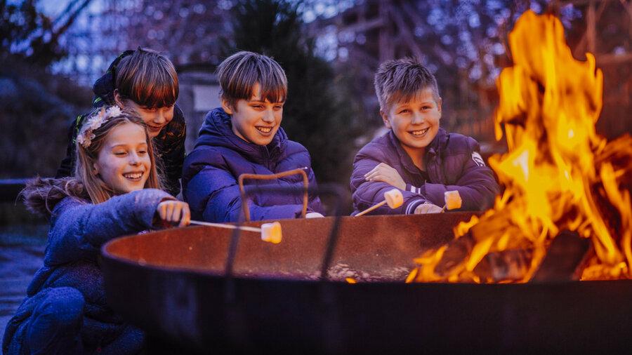 Kinderen roosteren marshmallows boven een kampvuur in Attractiepark Toverland