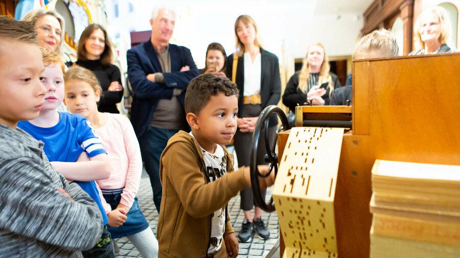 Jongen draait aan draaiorgel in Museum Speelklok
