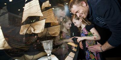 Vader en dochter bekijken een modelschip in een vitrine