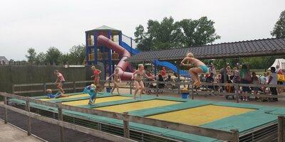 Kinderen springen op de trampolines van Speelboerderij de Flierefluiter