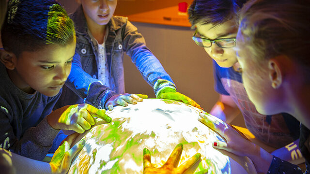 Kinderen zoeken op wereldbol bij Geofort
